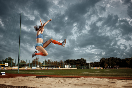Foto de Female athlete performing a long jump during a competition at stadium. The jump, athlete, action, motion, sport, success, championship concept - Imagen libre de derechos