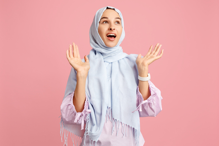 Photo for Happy surprised arab woman in hijab. Portrait of smiling girl, posing at pink studio background. Young emotional woman. The human emotions, facial expression concept. Front view. - Royalty Free Image