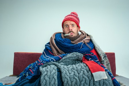 Photo for Bearded sick man with flue sitting on sofa at home or studio with thermometer covered with knitted warm clothes. Illness, influenza concept. Relaxation at Home. Healthcare Concepts. - Royalty Free Image