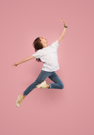 Foto de Always on mobile. Full length of pretty young woman taking phone and making selfie while jumping against pink studio background. Mobile, motion, movement, business concepts - Imagen libre de derechos