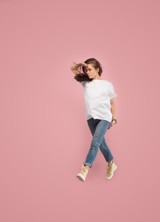 Photo for What is there interesting in the distance. seeking pretty happy young woman jumping and gesturing against pink studio background. Runnin girl in motion or movement. Human emotions and facial expressions concept - Royalty Free Image