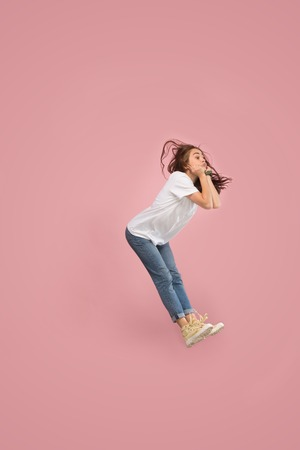 Photo for What is there interesting in the distance. seeking pretty happy young woman jumping and grabbing against pink studio background. Runnin girl in motion or movement. Human emotions and facial expressions concept - Royalty Free Image