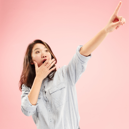 Photo for Wow. Beautiful female half-length front portrait isolated on pink studio backgroud. Young emotional surprised woman standing and pointing up. Human emotions, facial expression concept. Trendy colors - Royalty Free Image
