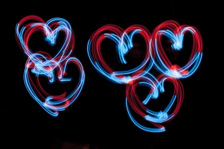 Foto de The hearts - -shaped digital neon lights are on the dark or black studio background - Imagen libre de derechos