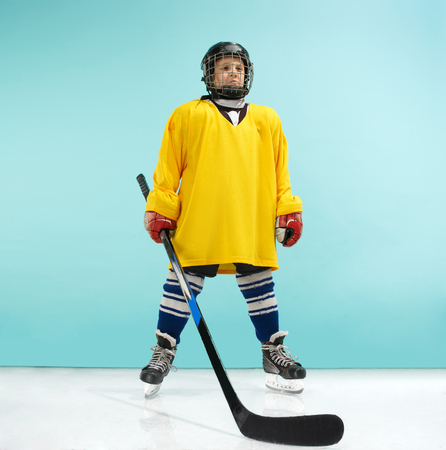 Photo for A hockey player in uniform with equipment over a blue studio background. The athlete, child, sport, action concept - Royalty Free Image