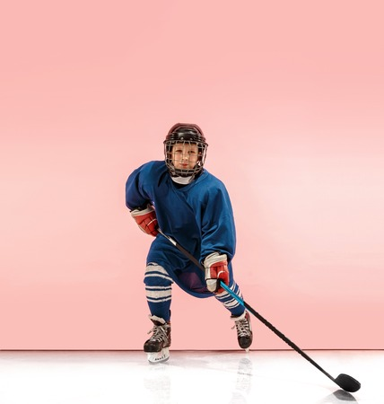 Photo for A hockey player in uniform with equipment over pink studio background. The athlete, child, sport, action concept - Royalty Free Image