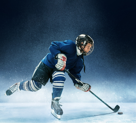 Foto de Little boy playing ice hockey at arena. A hockey player in uniform with equipment over a blue background. The athlete, child, sport, action concept - Imagen libre de derechos