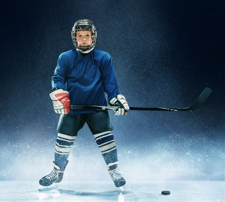 Photo for Little boy playing ice hockey at arena. A hockey player in uniform with equipment over a blue background. The athlete, child, sport, action concept - Royalty Free Image