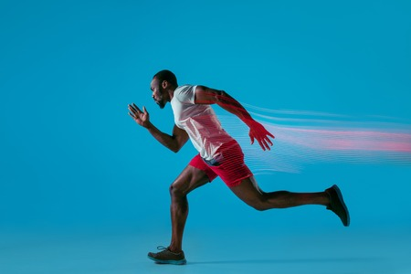 Foto de Full length portrait of active young african muscular running man, isolated over blue studio background with flashes of light - Imagen libre de derechos