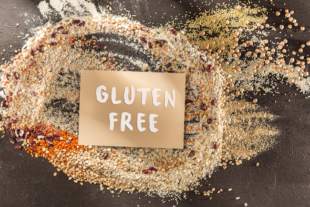 Foto de Gluten free flour and cereals millet, quinoa, corn bread, brown buckwheat, rice, bread and pasta with text gluten free in English language with spoon on wooden background, top view - Imagen libre de derechos
