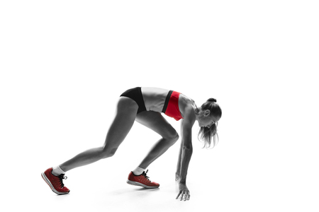 Photo pour Portrait of young sporty woman at starting block of race isolated over white studio background. The sprinter, jogger, exercise, workout, fitness, training, jogging concept. Profile - image libre de droit