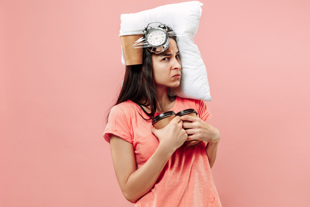 Foto de Tired happy woman with coffee at home or office having too much work. Bored businesswoman with pillow and coffee cups. The busy, boring, worried, be late, concerned, sleep day, introuble concept - Imagen libre de derechos