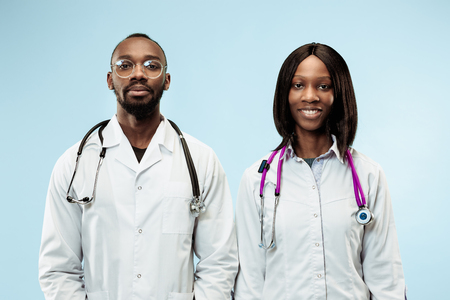 Foto de The female and male smiling happy afro american doctors on blue background at studio.The clinic, medical, nurse, health, healthcare, hospital, care, job, professional concept - Imagen libre de derechos