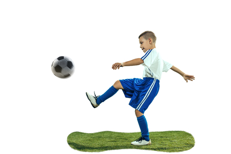 Foto de Young boy kicks the soccer ball. Isolated photo on white background. Football player in motion at studio. Fit jumping boy in action, jump, movement at game. - Imagen libre de derechos