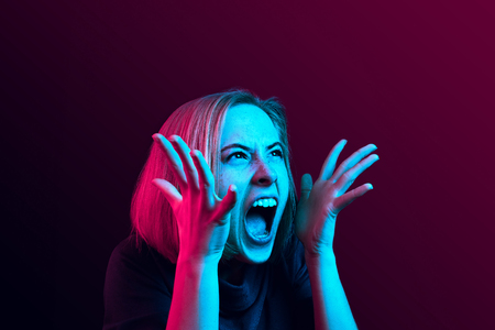 Photo pour Screaming, hate, rage. Crying emotional angry woman screaming on neon studio background. Emotional, young face. Female half-length portrait. Human emotions, facial expression concept. Trendy colors - image libre de droit