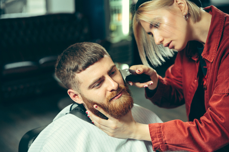 Photo pour Client during beard shaving in barbershop. Female barber at salon. Gender equality. Woman in the male profession. - image libre de droit