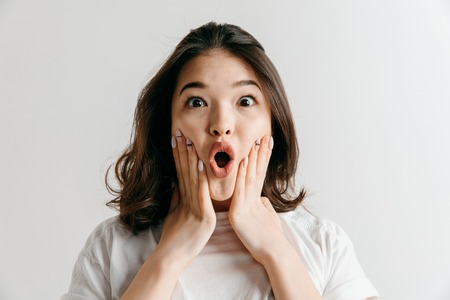 Foto de Wow. Beautiful female half-length front portrait isolated on gray studio backgroud. Young emotional surprised asian woman standing with open mouth. Human emotions, facial expression concept. - Imagen libre de derechos