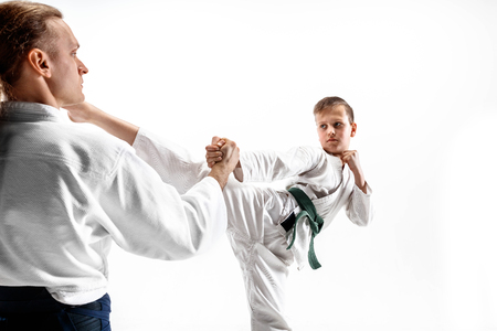 Foto de Man and teen boy fighting at Aikido training in martial arts school. Healthy lifestyle and sports concept. Fightrers in white kimono on white background. Karate men with concentrated faces in uniform. - Imagen libre de derechos