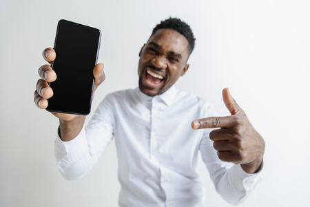 Foto de Indoor portrait of attractive young black african man isolated on grey background, holding blank smartphone, smiling at camera, showing screen, feeling happy and surprised. Human emotions, facial - Imagen libre de derechos