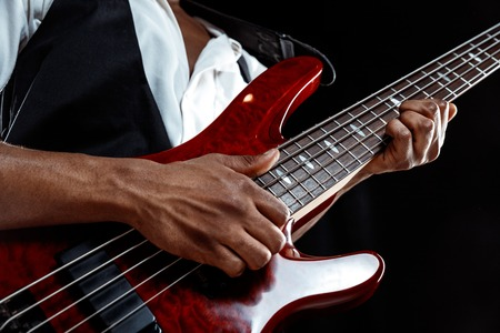 Photo for African American handsome jazz musician playing bass guitar in the studio on a black background. Music concept. Young joyful attractive guy improvising. Close-up retro portrait. - Royalty Free Image