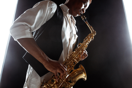 Photo for African American handsome jazz musician playing the saxophone in the studio on a black background. Music concept. Young joyful attractive guy improvising. Close-up retro portrait. - Royalty Free Image