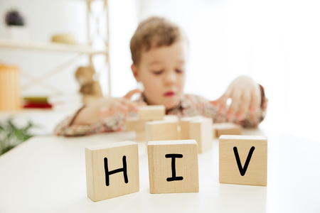 Foto de Wooden cubes with word HIV in hands of little boy at home. Symbol of the fight against AIDS and cancer. Concept of helping those in need - Imagen libre de derechos