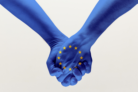 Foto de Peace and strong. Male hands holding colored in blue EU flag isolated on gray studio background. Concept of help, commonwealth, unity of European countries, political and economical relations. - Imagen libre de derechos