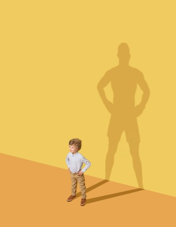 Foto per I could protect my family. Future champion. Childhood and dream concept. Conceptual image with child and shadow on the yellow studio wall. Little boy want to become a boxer and to build a sport career. - Immagine Royalty Free