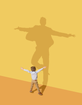 Photo for Succesfull. Childhood and dream concept. Conceptual image with child and shadow on the yellow studio wall. Little boy want to become ballet dancer, artist in theatre or businessman, office man. - Royalty Free Image