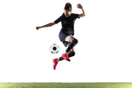 Foto de Young female soccer or football player with long hair in sportwear and boots kicking ball for the goal in jump isolated on white background. Concept of healthy lifestyle, professional sport, hobby. - Imagen libre de derechos