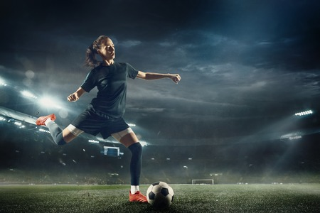 Photo for Young female soccer or football player with long hair in sportwear and boots kicking ball for the goal in jump at the stadium. Concept of healthy lifestyle, professional sport, hobby, motion, movement. - Royalty Free Image