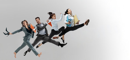 Photo pour Happy office workers jumping and dancing in casual clothes or suit with folders isolated on studio background. Business, start-up, working open-space, motion and action concept. Creative collage. - image libre de droit