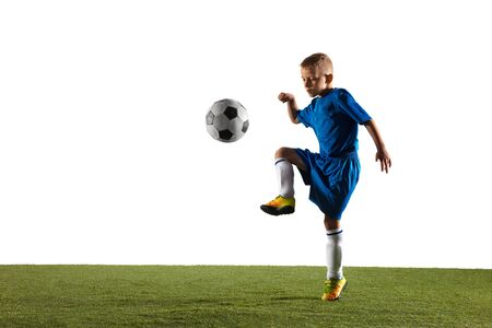 Photo for Young boy as a soccer or football player in sportwear making a feint or a kick with the ball for a goal on white studio background. Fit playing boy in action, movement, motion at game. - Royalty Free Image