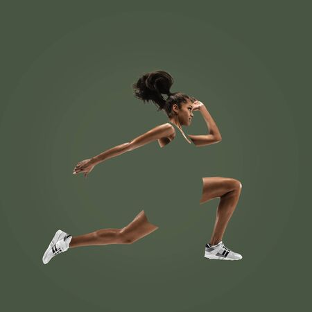 Foto de Young african woman running isolated on green studio background. One female runner or jogger. Silhouette of jogging athlete. Concept of healthy lifestyle, sport, movement, action. Abstract design. - Imagen libre de derechos