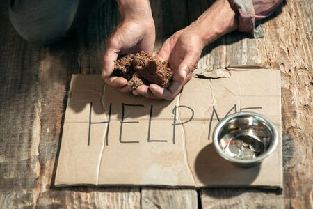 Photo for Male beggar hands seeking money with sign HELP ME from human kindness on the wooden floor at public path way or street walkway. Homeless poor in the city. Problems with finance, place of residence. - Royalty Free Image