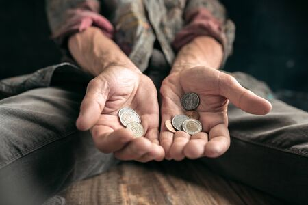 Photo for Male beggar hands seeking money, coins from human kindness on the wooden floor at public path way or street walkway. Homeless poor in the city. Problems with finance, place of residence. - Royalty Free Image