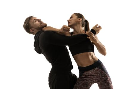 Foto de Man in black outfit and athletic caucasian woman fighting on white studio background. Womens self-defense, rights, equality concept. Confronting domestic violence or robbery on the street. - Imagen libre de derechos