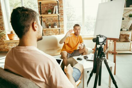 Photo for Two young caucasian male bloggers in casual clothes with professional equipment or camera recording video interview at home. Blogging, videoblog, vlogging. Talking while streaming live indoors. - Royalty Free Image