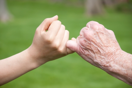 Foto de Senior and Young Hands Promise - Imagen libre de derechos