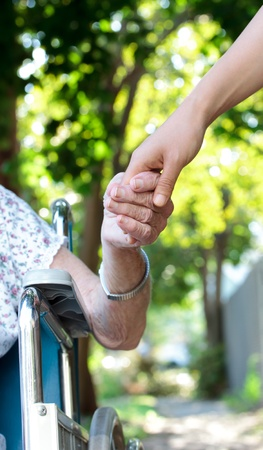 Photo for Holding hands with senior lady in wheelchair - Royalty Free Image