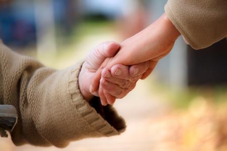 Photo pour Senior and young holding hands outside - image libre de droit