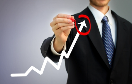 Businessman highlighting business growth on a graph