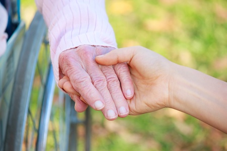 Photo for Senior Lady in Wheelchair Holding Hands with a Young Caretaker or Loved-one - Royalty Free Image