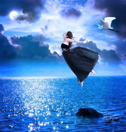Photo pour Beautiful girl jumping into the blue night sky with white egret - image libre de droit