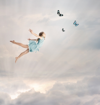 Photo for Little Blonde Girl Flying with Butterflies at Twilight  - Royalty Free Image