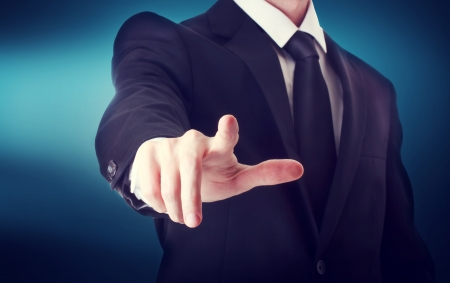Photo pour Business man with pointing to something or touching a touch screen on blue background - image libre de droit