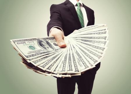 Photo pour Business Man Displaying a Spread of Cash over a green vintage background - image libre de droit