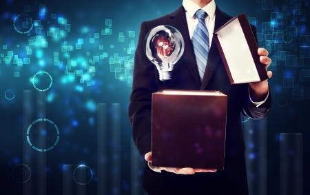 Foto de Business man opening box with an idea lightbulb on blue technology background - Imagen libre de derechos