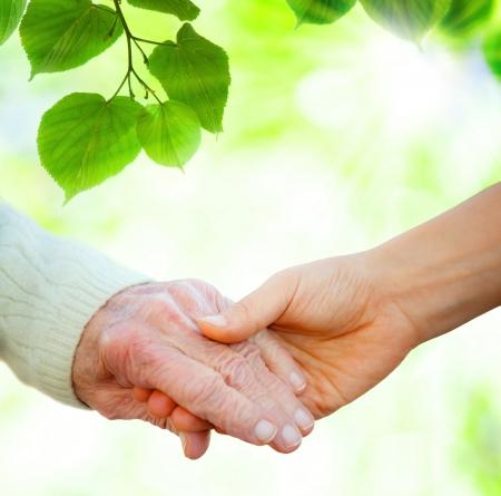 Photo pour Holding hands with senior over green leaves  - image libre de droit