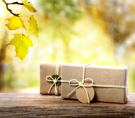 Photo for Handcrafted gift boxes on aged  wooden boards with an autumn foliage  - Royalty Free Image
